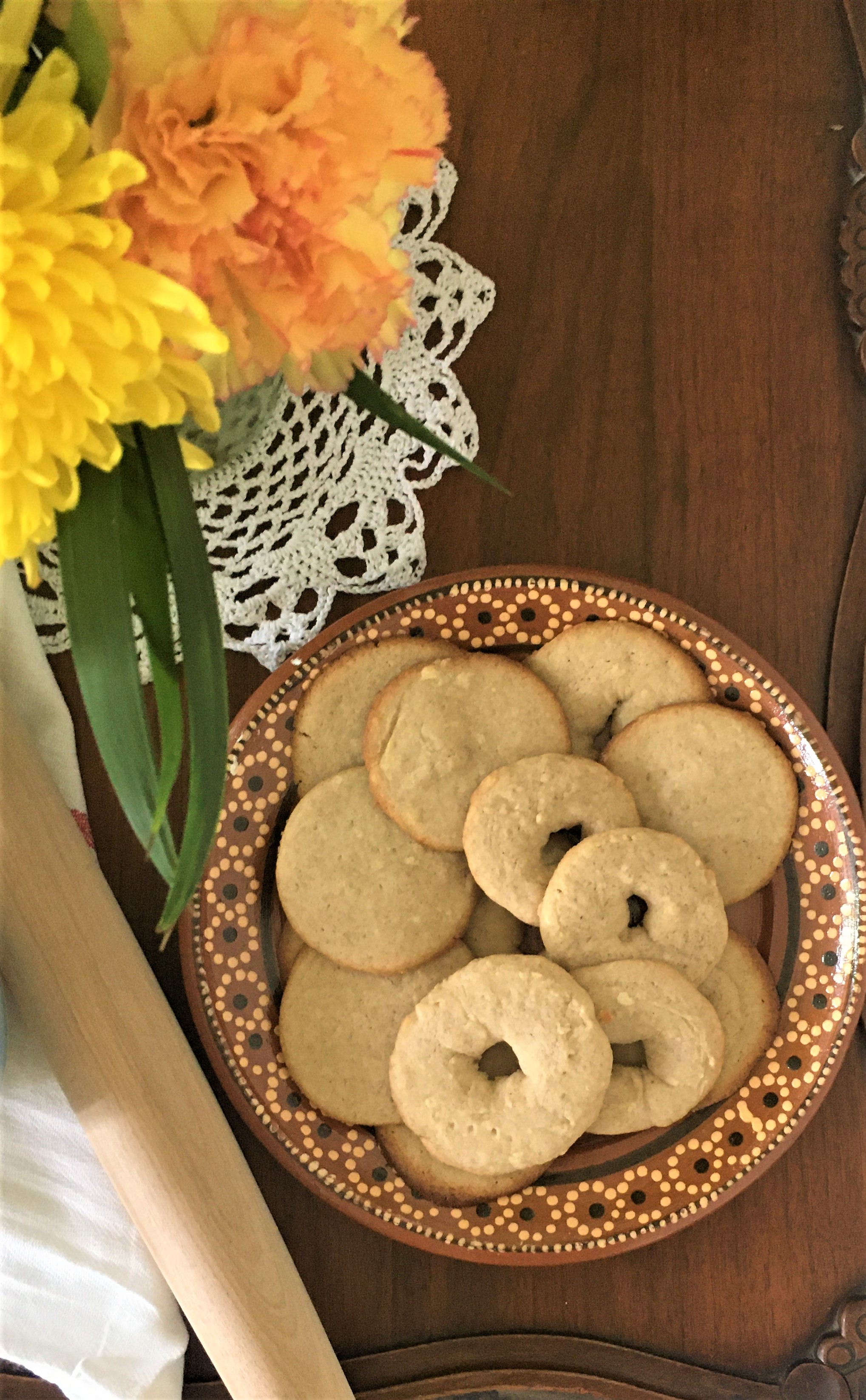An image of Jumble cookies on a clay plate, sitting on a wooden table with orange & yellow flowers and a wooden rolling pin off to the side.